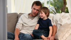 Attentive father watching tv with his son Stock Footage