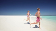 Couple running into waves Stock Footage