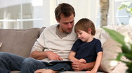 Stock Video Footage of Nice father reading a story to his young son