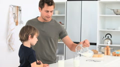 Attentive man serving a glass of milkto his son Stock Footage