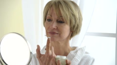 Beautiful Mature Woman Applying Moisturizer; HD Photo JPEG, dolly.  Stock Footage