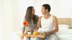 Man drinking orange juice while he having breakfast with his wife Stock Footage