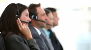 Smiling customer service agents working in a call center Stock Footage