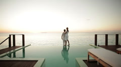 Couple on private pool watching sunset Stock Footage
