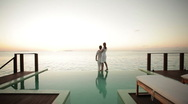 Stock Video Footage of couple on private pool watching sunset