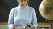 Stock Video Footage of Female teacher reading in classroom; HD Photo JPEG