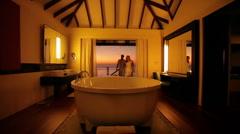 Couple entering bungalow bathroom Stock Footage