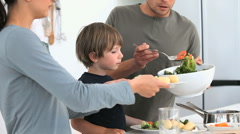 Man serving a salad to his family for lunch Stock Footage