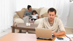 Worried man calculating bills while his wife reads a book to their daughter Stock Footage