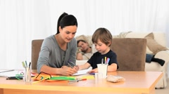 Attentive mother drawing with her son while father sleeps - stock footage