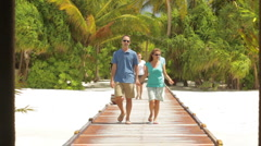 Two couples walking on tropical pier Stock Footage