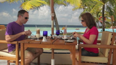 couple having lunch on a tropical beach terrace - stock footage