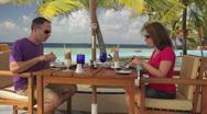 Couple having lunch on a tropical beach terrace Stock Footage