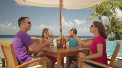 Family cheering with drinks on tropical terrace Stock Footage