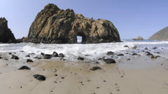 Low angle time lapse of waves breaking through a rock at Pfeiffer Beach Stock Footage