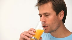 Man drinking a glass of orange juice - stock footage