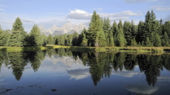 Time lapse of clouds, mountains and forest reflecting at Schwabacher Landing Stock Footage