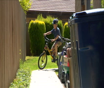 Cute little boy leaves house riding bike Stock Footage