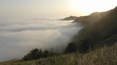 Time lapse of sun setting over fog rolling against the mountains at Big Sur Stock Footage