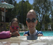 Little boy & girl surface in pool - stock footage