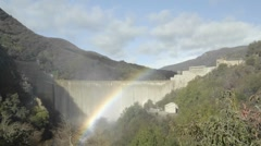 Wide time lapse of a rainbow moving across water spilling over the Matilija Dam Stock Footage