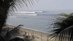 Time lapse of waves breaking framed by palms at La Saladita Beach in Guerrero Stock Footage