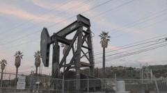 Oil pumpjack increasing speed while pumping in Ventura, California. Stock Footage