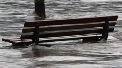Park bench in flooded river Stock Footage