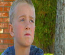 Cute blonde little boy day dreaming Stock Footage