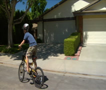 Profile of little boy riding his bike on suburban street Stock Footage