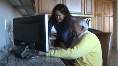 Caring caregiver/young woman looks at computer with elderly man-laughing - stock footage
