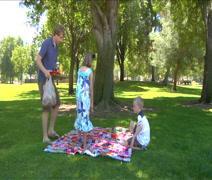 Kids lay out blanket for family picnic in a park Stock Footage