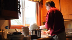 Man Washing Dirty Dishes in the kitchen sink inside of his home - stock footage