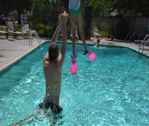 Father tosses daughter with pink flippers into pool Stock Footage