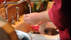 Man Cleaning Dirty Dishes in the kitchen sink - stock footage