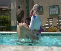 Father plays with 3 kids in family swimming pool Stock Footage