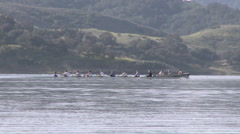 Panning an eight person rowing sweep being followed by their coach Stock Footage