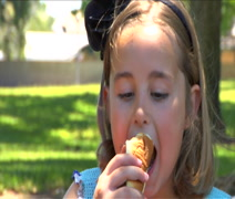 Little girl bites hot dog and smiles to camera Stock Footage