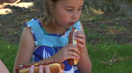 Little girl eating hot dog at Family Picnic Stock Footage
