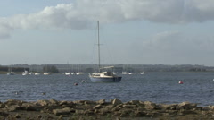 Yacht moored to buoy on Rutland Water turns on wind. Stock Footage
