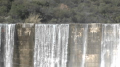 Zoom out of water spilling over the Matilija Dam after a rain in Ojai Stock Footage
