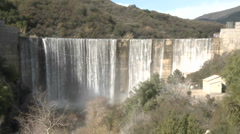 Wide zoom out of water spilling over the Matilija Dam after a rain in Ojai Stock Footage