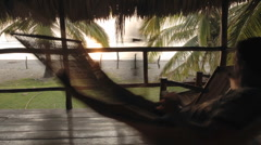Time lapse of man sitting in a hammock in palapa at La Saladita Beach, Guerrero Stock Footage