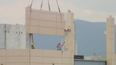 Precast concrete panel hoisted into place Stock Footage