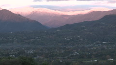 Wide zoom out of sunrise on the snow-covered Santa Ynez Mountains above Ojai Stock Footage