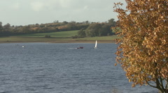 Dinghies beyond autumn tree - Rutland Water. Stock Footage