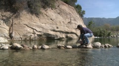 Man removing rocks from a fish barrier on the Ventura River Preserve in Ojai Stock Footage