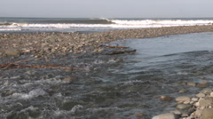 Water flowing out of the Ventura River estuary into the Pacific Ocean Stock Footage
