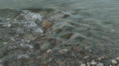 Tilt up of water flowing out of the Ventura River estuary and waves  Stock Footage