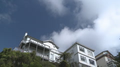 Houses on a hill and fast clouds time lapse Stock Footage